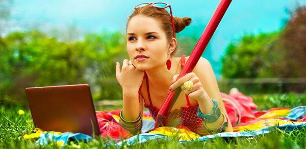 Девушка лежит на траве с ноутбуком и карандашом
