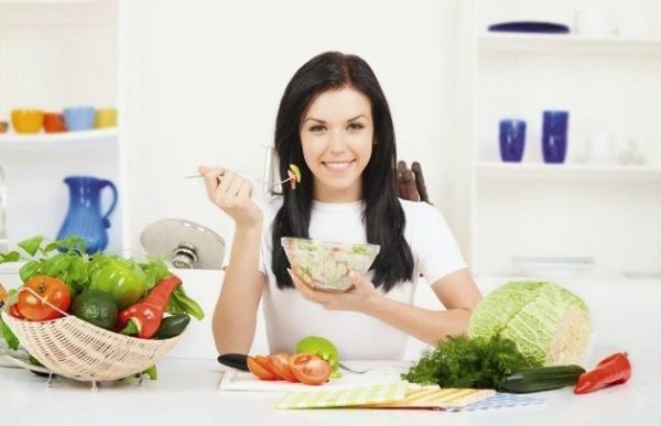 Девушка за столом ест салат