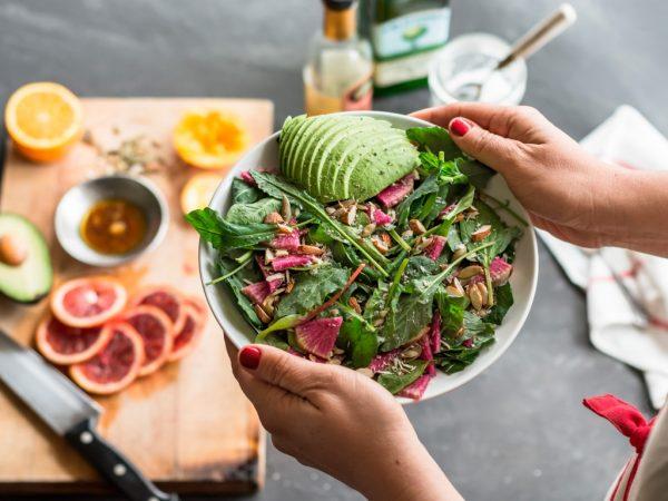 Девушка несёт салат в тарелке
