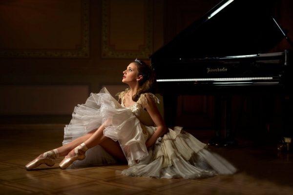 Балерина сидит на полу рядом с роялем