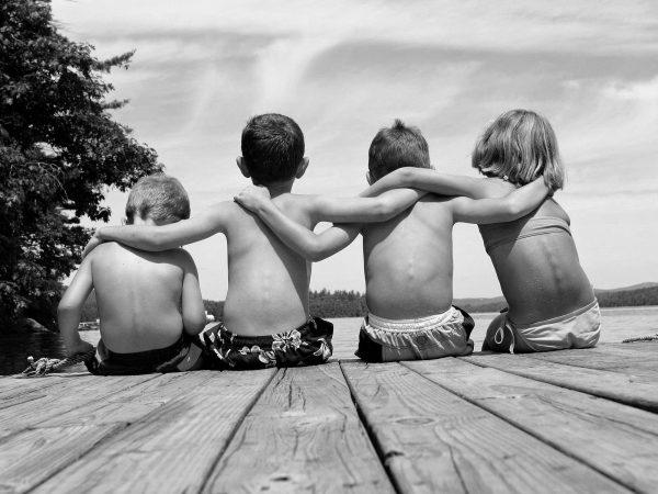 Девочка и три мальчика сидят на берегу