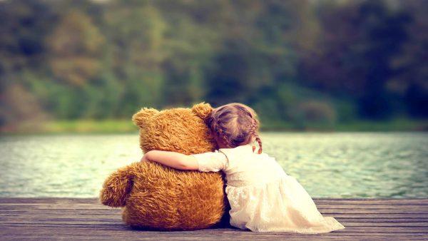 Девочка с игрушкой сидит на берегу реки