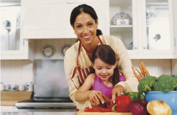Девочка с мамой готовят на кухне