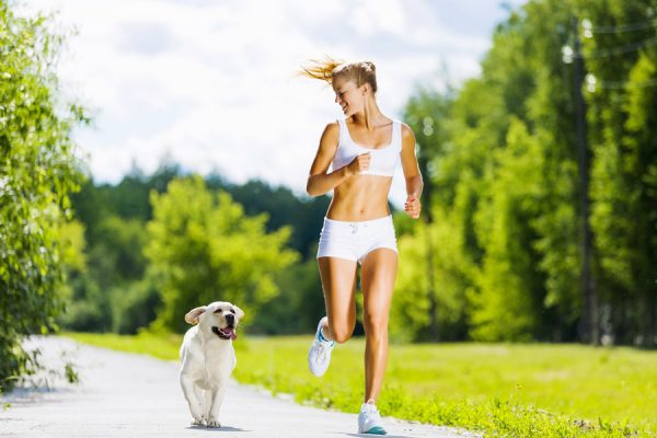 Девушка бежит в парке с собакой