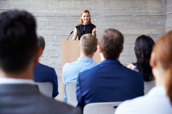 Девушка говорит речь перед публикой