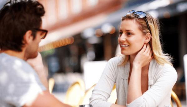 девушка с мужчиной беседуют на улице в кафе
