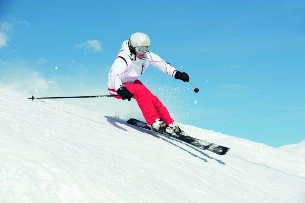Девушка спускается с горы на лыжах