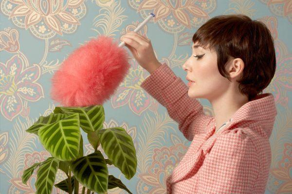 Девушка убирает пыль с цветка