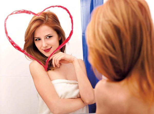 Девушка улыбается своему отражению в зеркале