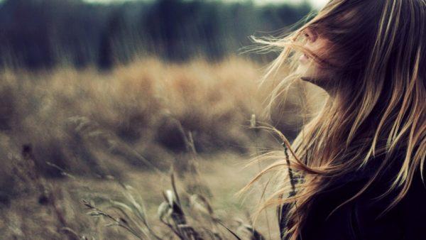 Девушка, волосы которой развевает ветер