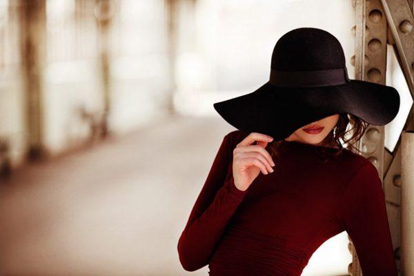 Девушка закрывает лицо шляпой