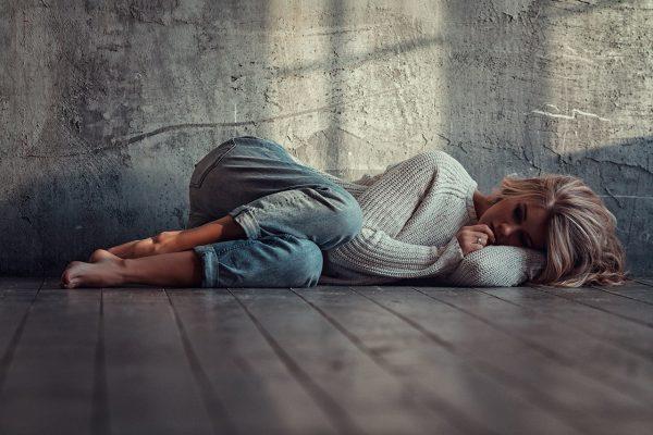 Грустная девушка лежит на полу