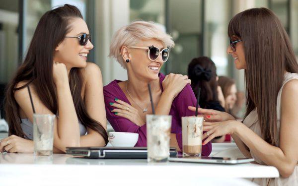 Три девушки общаются в кафе