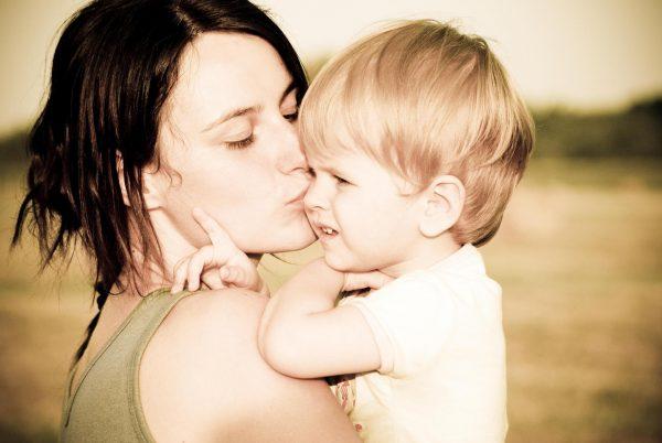 Женщина целует сына