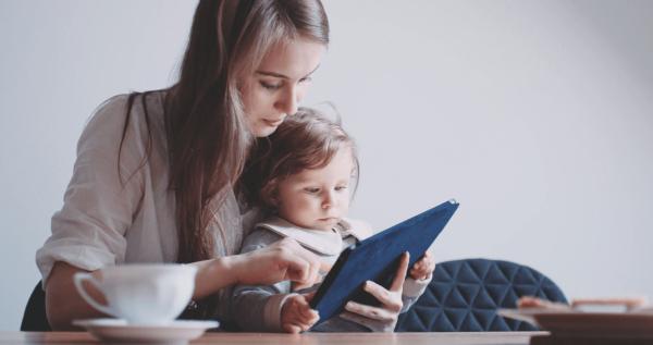 Женщина с ребёнком смотрят в планшет
