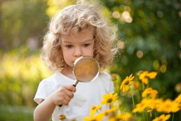 Девочка разглядывает цветок под лупой