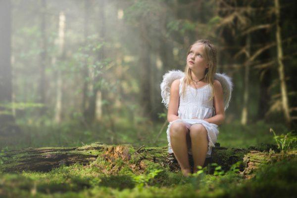 Девочка с ангельскими крыльями в лесу
