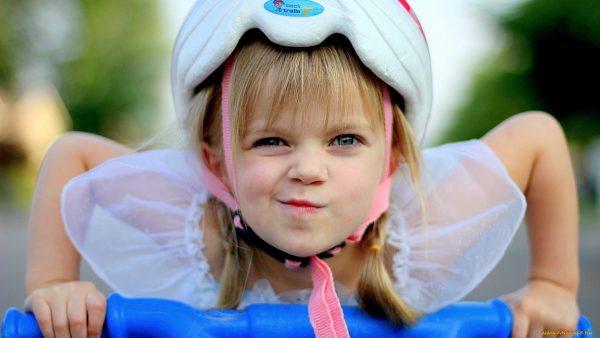 Девочка в шлеме едет на велосипеде
