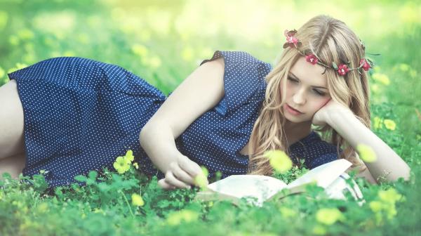 Девушка лежит на траве и читает книгу