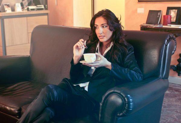 Девушка на диване с чашкой кофе