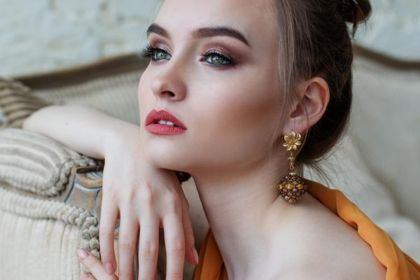 Девушка на диване с красивой серьгой