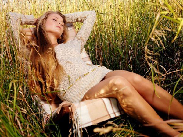 Девушка отдыхает в кресле в густой траве
