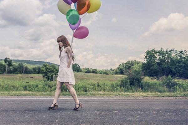 Девушка с шариками идёт по дороге