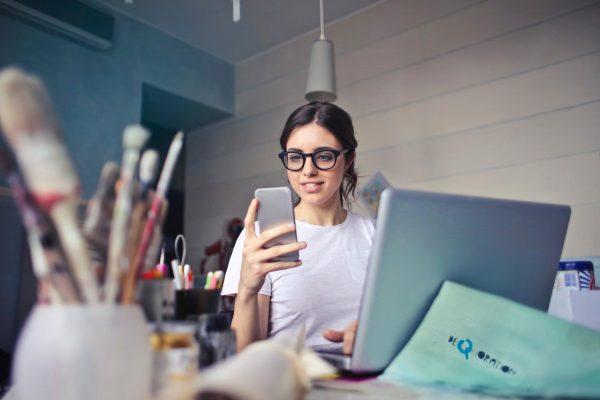 Девушка с телефоном за ноутбуком
