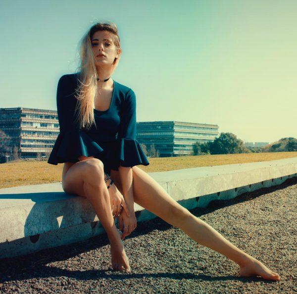 Девушка сидит на фоне домов
