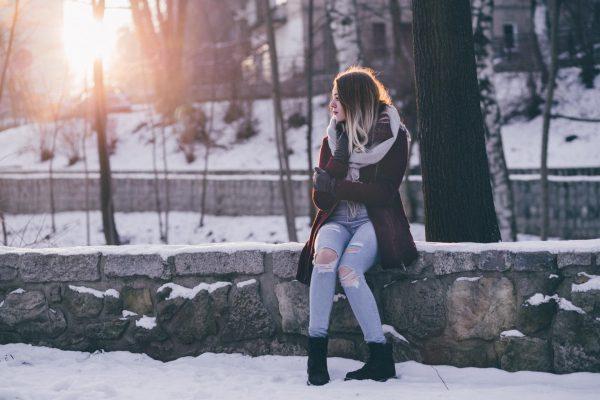 Девушка сидит на каменном заборчике