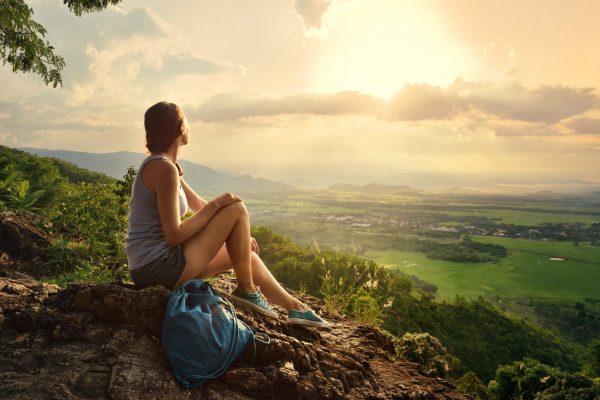 Девушка сидит на вершине горы