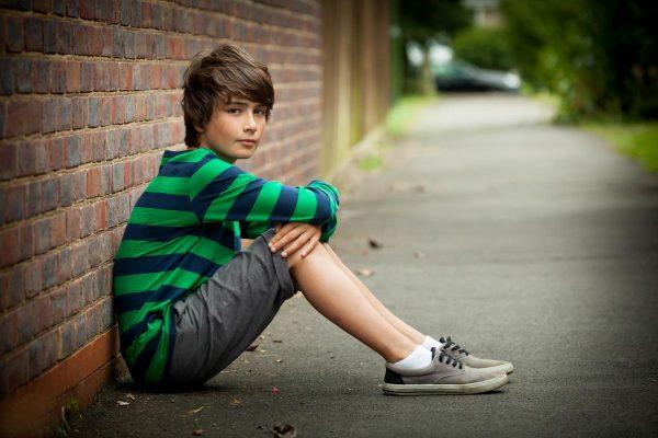 Мальчик сидит на асфальте