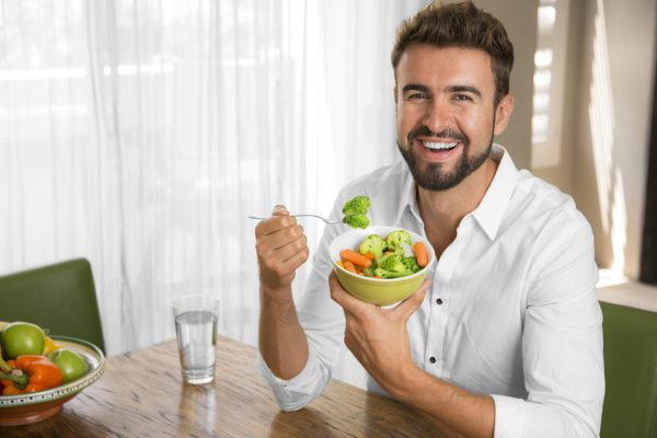Мужчина ест овощи