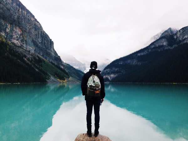 Мужчина с рюкзаком смотрит на красивый пейзаж