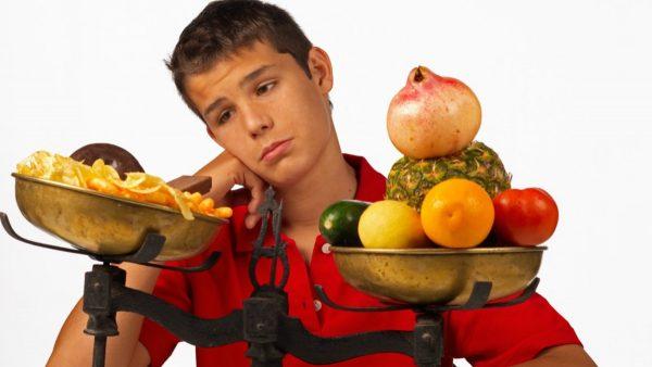 Парень и весы с фастфудом и фруктами/овощами