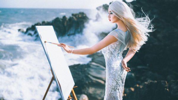 Девушка на побережье рисует на мольберте