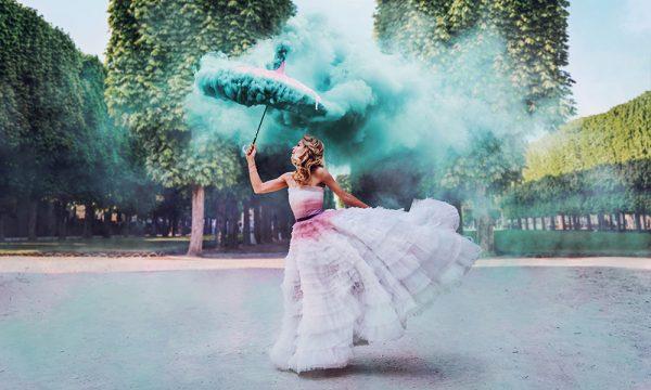 Девушка в красивом платье с дымящимся зонтом