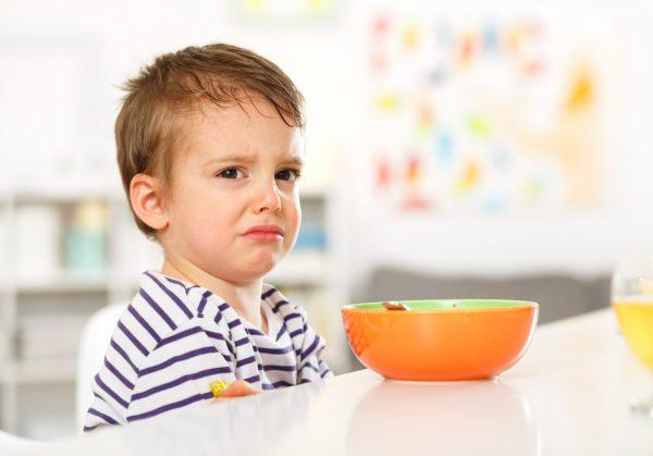 Грустный мальчик за столом с едой