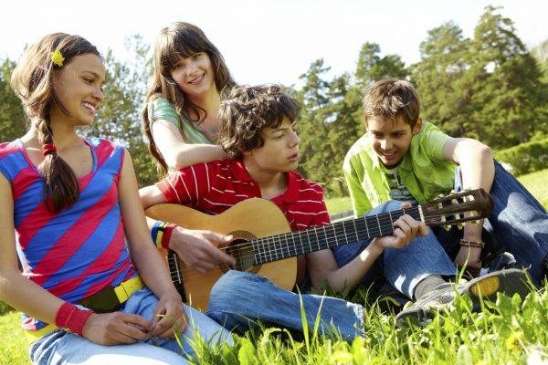 Компания подростков с гитарой сидят на траве