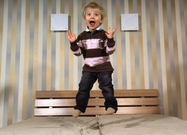 Мальчик прыгает на кровати