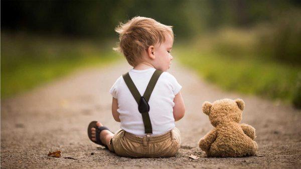 Мальчик сидит на дороге с игрушкой
