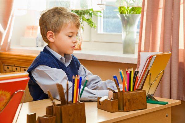 Мальчик сидит за партой в школе
