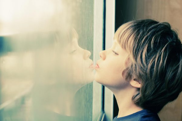 Мальчик стоит у окна