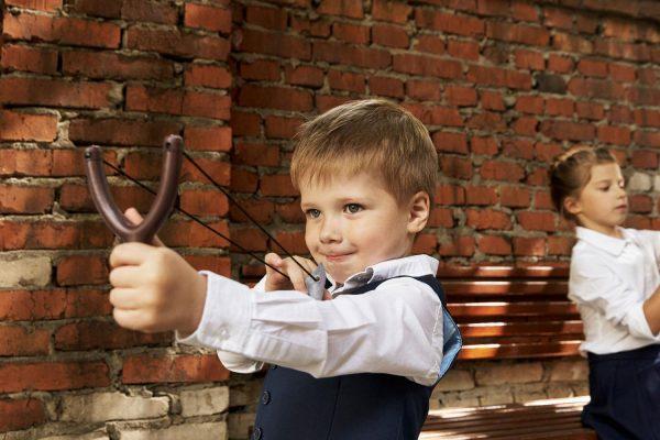 Мальчик стреляет из рогатки