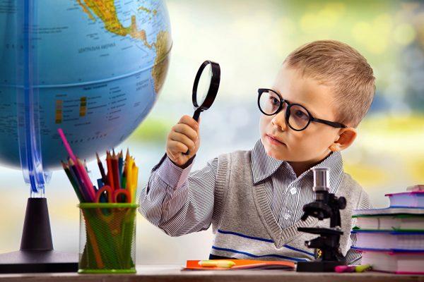 Мальчик в очках изучает глобус