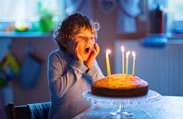Мальчик задувает свечи