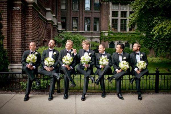 Мужчины с букетами сидят на ограде