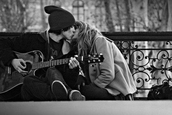 Молодой человек с гитарой целует девушку