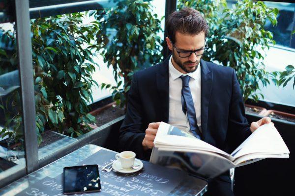Мужчина читает газету за чашкой кофе