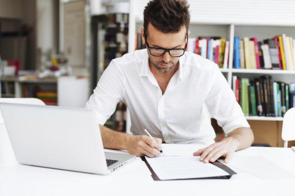 Мужчина с ноутбуком и тетрадью